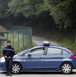A gendarme blocks access to the site where four people were shot dead near Chevaline in the French Alps (AP)