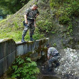 French police inspect a drain under the road to the murder scene at Cheverlaine near Annecy