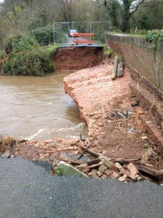 A collapsed road bridge over the swollen River Culm on the B3181 between Bradninch and Westcott