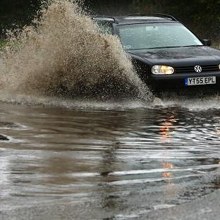 A motorist drives through floodwaters in Chichester, West Sussex, as forecasters predict a prolonged period of wet weather through Christmas