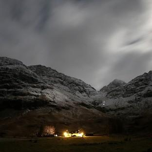 Climbers make their way off Bidean nam Bian in the Scottish Highlands by torchlight