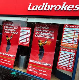 A masked armed robber collapsed and died after being disarmed and pinned down by customers in a Ladbrokes bookies