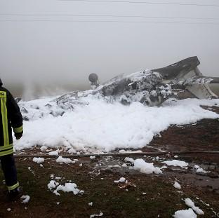 Mid Devon Star: A firefighter stands next to the burnt-out wreckage of a twin-engine business jet near Foehren, Germany (AP)