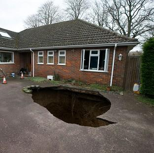 Mid Devon Star: The home of Phil and Liz Conran, High Wycombe, after a 30ft-deep sinkhole opened up in the driveway and swallowed their car