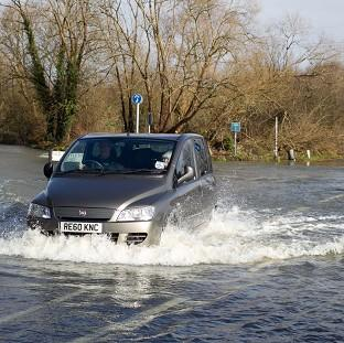 A car drives through flood water as the River Thames burst its bank and flooded roads and property in Chertsey in Surrey