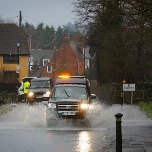 Mid Devon Star: A car passes through a flooded road in Yalding, Kent