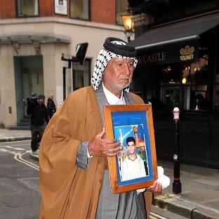 Mid Devon Star: Mizal Karim Al-Sweady, the father of Hamid Al-Sweady carries a photo of his son after leaving the inquiry into his death.