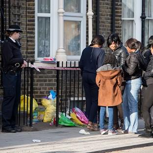 A police officer watches as a group of people gather at the scene in Hackney where She