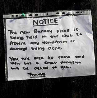 Mid Devon Star: A notice sits where the latest officially confirmed Banksy artwork was, on Clements Street in Bristol