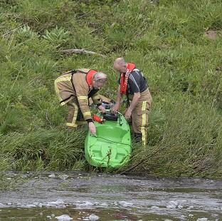 Mid Devon Star: Rescue services retrieve a kayak at Riding Mill Pumping station on the River Tyne in Northumberland where three kayakers died