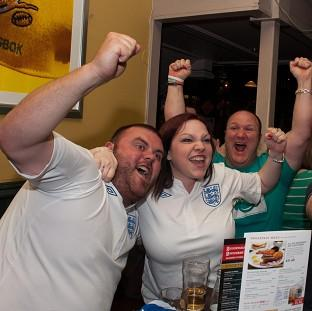 Mid Devon Star: England fans cheer their team in the pub