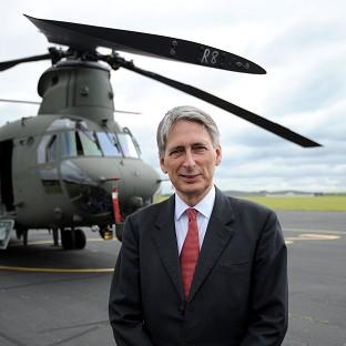 Mid Devon Star: Defence secretary Philip Hammond stands in front of the new Chinook Mk6 helicopter during its unveiling at RAF Odiham in Hampshire