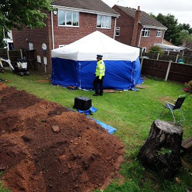 Mid Devon Star: Police in the garden of a house in Mansfield, where the remains of William and Patricia Wycherley were discovered